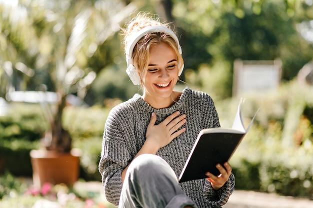 Close-upportret van vrouw die aan muziek luistert en een boek leest