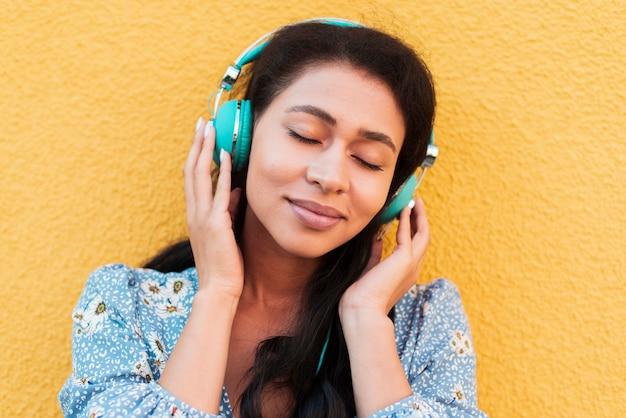 Close-upportret van vrouw die aan muziek luistert