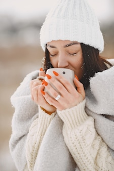 Close-upportret van vrouw in witte sweater met thee