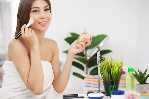 Close-upportret van vrouw met make-upborstel dichtbij gezicht.