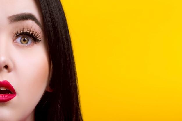 Close-upportret van vrouw verrast, met rode lippen op gele muur