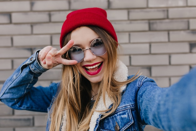 Close-upportret van zalig wit meisje dat pret heeft openlucht. schattige blonde vrouwelijke model dansen en selfie maken op bakstenen muur.