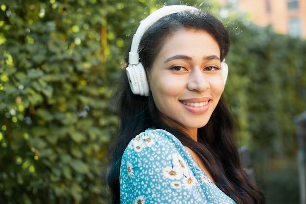 Close-upportret van zijdelings vrouw met hoofdtelefoons