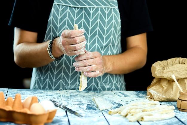 Close-upproces dat zelfgemaakte pasta maakt. chef kok snijden met mes