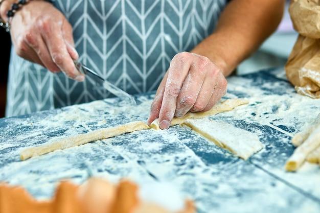 Close-upproces die eigengemaakte deegwaren maken. chef kok snijden met mes