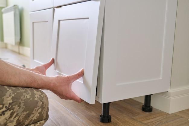 Close-upproces om keukenmeubilair, handen van mannelijke arbeider te assembleren