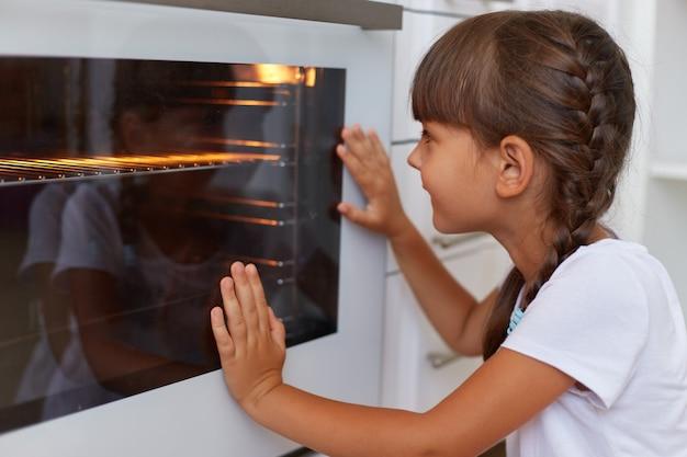 Close-upprofielportret van donkerharig klein schattig charmant vrouwtje dat naar de oven kijkt, wachtend wanneer het bakken klaar zal zijn, kind dat een wit casual stijlt-shirt draagt.