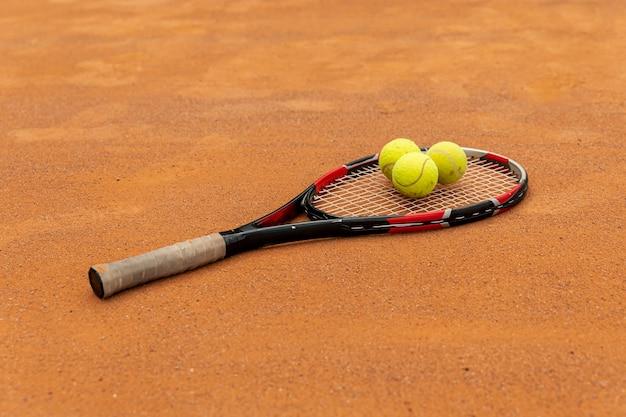 Close-upracket en tennisballen op hofgrond