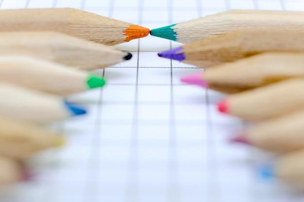 Close-upreeks kleurrijke potloden op het geruite document blad van notitieboekje voor de tekening. terug naar school-concept.