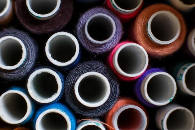 Close-upreeks strengen van multi-coloured naaiende draad. de industrie van de staart.