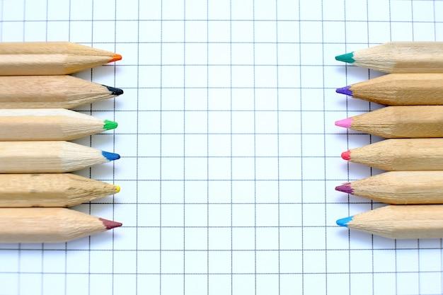 Close-upreeks veelkleurige potloden op het geruite document blad van notitieboekje voor de tekening. terug naar school-concept.