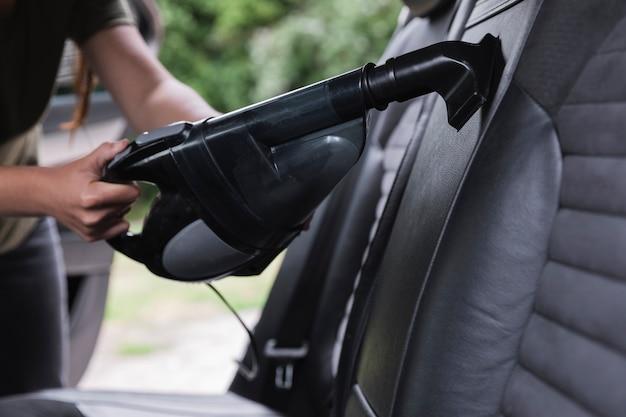 Close-upschot die de auto met stofzuiger schoonmaken