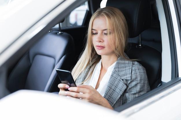 Close-upschot met een blondevrouw die telefoon bekijken
