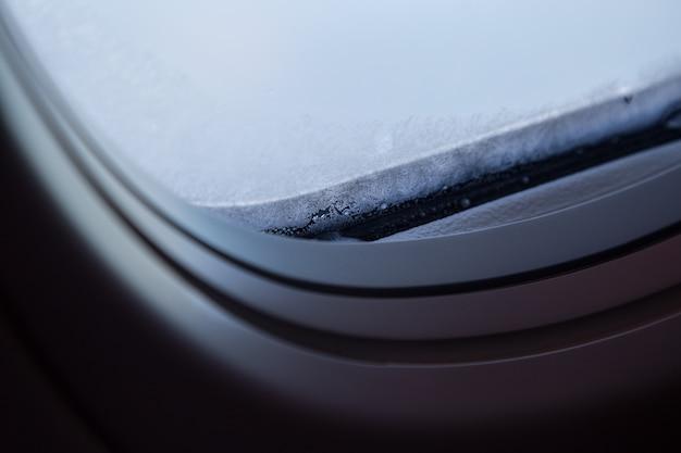 Close-upschot van bevroren vensterglas in vliegtuig.