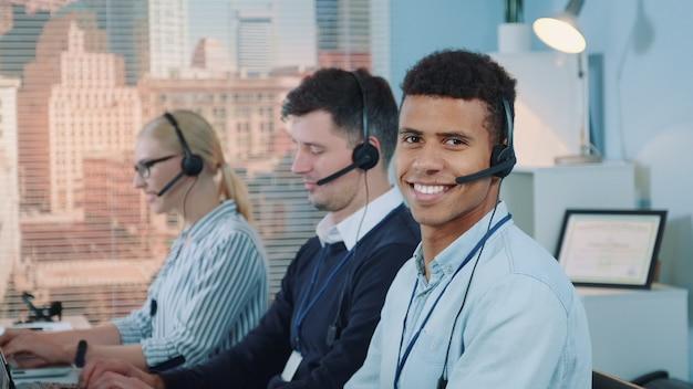 Close-upschot van de glimlachende gemengd rasmens die oproep in bezig call centre nemen