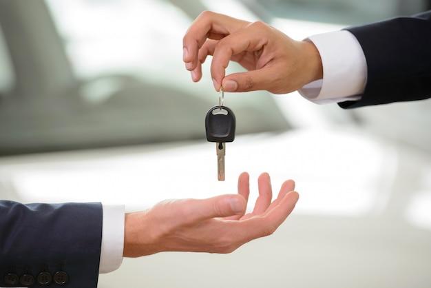 Close-upschot van de hand die van de autoverkoper sleutel geeft aan eigenaar.