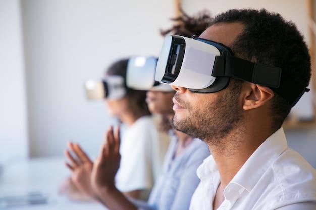 Close-upschot van de jonge mens die virtuele werkelijkheidshoofdtelefoon testen