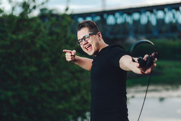 Close-upschot van de toevallige jonge mens in hipsterglazen met hoofdtelefoons op de achtergrond van de de zomeraard