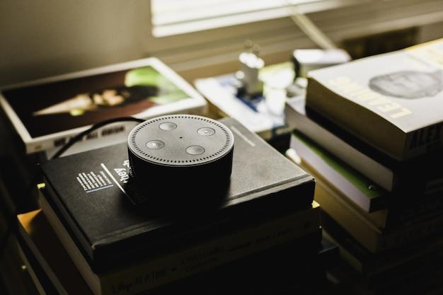 Close-upschot van een rond zwart klein audiocontroleapparaat op boeken binnen