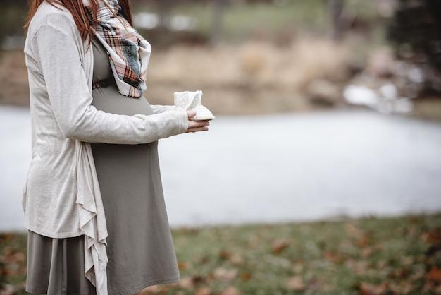 Close-upschot van een zwangere babyschoenen van de vrouwenholding