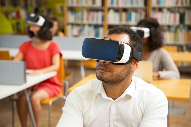 Close-upschot van geconcentreerde jonge kerel met virtuele werkelijkheidshoofdtelefoon