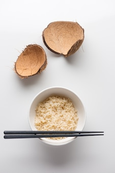 Close-upschot van gekookte rijst in een witte plastic kom met eetstokjes op het op een wit