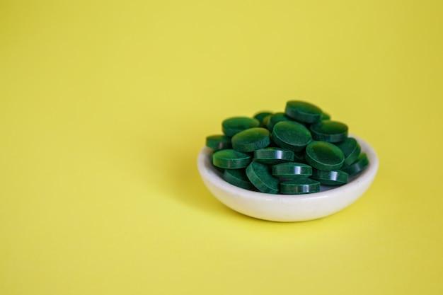 Close-upstapel van groene spirulinapillen