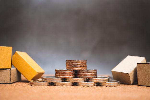 Close-upstapel van muntstukken en kartondozen die als bedrijfs en logistiekconcept gebruiken