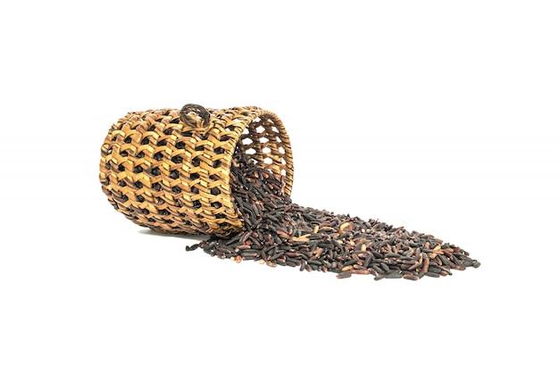 Close-upstapel van zwarte rijst genoemd riceberry rijst met houten mandewerk, rijst met hoge die voedingsmiddelen op wit worden geïsoleerd