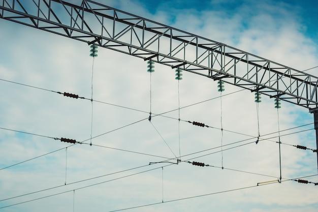 Close-upsteun van het elektrische netwerk van de contactspoorweg tegen bewolkte blauwe hemel