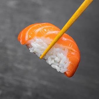 Close-upstokken die smakelijke sushi houden