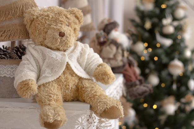 Close-upstuk speelgoed teddybeer op een schoorsteenmantel op een vage achtergrond van een verfraaide kerstboom.