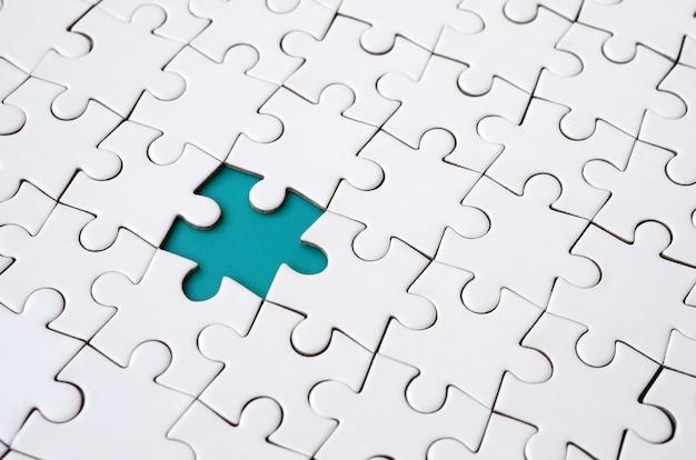 Close-uptextuur van een witte puzzel in samengestelde staat met ontbrekende elementen die een blauw stootkussen voor tekst vormen. ruimte kopiëren