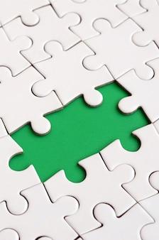 Close-uptextuur van een witte puzzel in samengestelde staat met ontbrekende elementen die een groen stootkussen voor tekst vormen. ruimte kopiëren