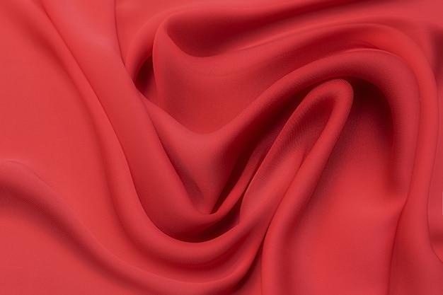 Close-uptextuur van natuurlijke rode of karmozijnrode of roze stof. stoffentextuur van natuurlijk katoen, zijde of wol, of linnen textielmateriaal. rode en oranje canvasachtergrond.