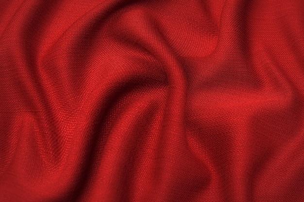 Close-uptextuur van natuurlijke rode of roze stof of doek in dezelfde kleur. stoffentextuur van natuurlijk katoen, zijde of wol, of linnen textielmateriaal. rode en oranje canvasachtergrond.