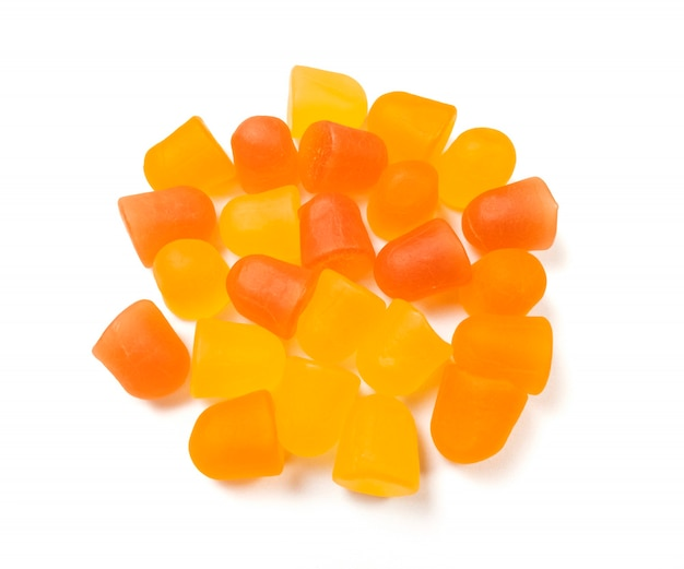 Close-uptextuur van oranje en gele multivitaminegummies op witte achtergrond. gezond levensstijlconcept.