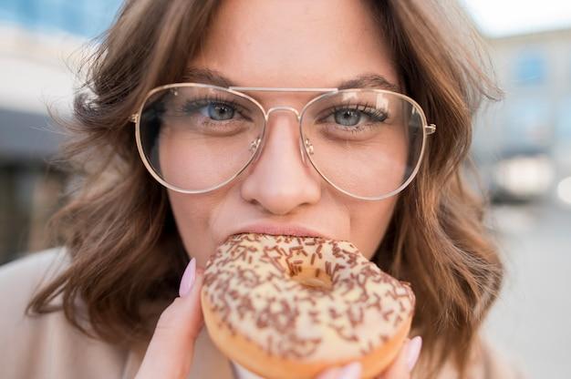 Close-uptiener die smakelijke doughnut eten