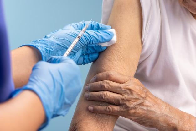 Close-upverpleegster die vaccininjectie doet aan hogere vrouw.