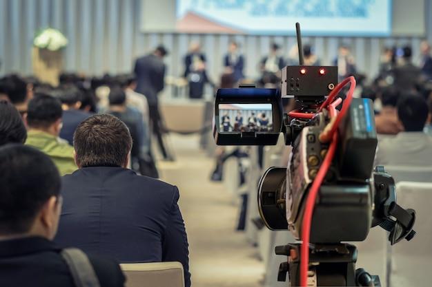 Close-upvideo die de spreker met formeel kostuum op het stadium over achtermening van audien registreren
