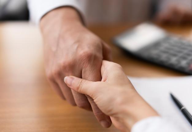 Close-upvolwassenen die handen schudden op het kantoor