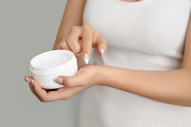 Close-upvrouw die beschermende room op handen toepast. handverzorging van de huid. cosmetische crème. schoonheids- en lichaamsverzorgingsconcept