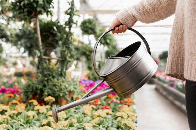 Close-upvrouw die de bloemen water geven