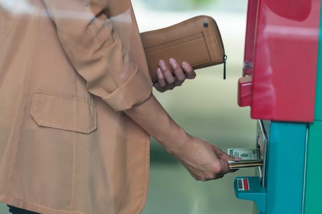 Close-upvrouw die de portefeuille houden en het contante geld terugtrekken via atm