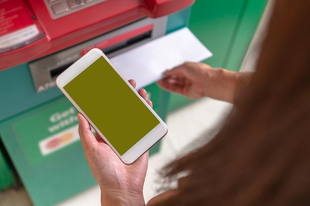 Close-upvrouw die de slimme mobiele telefoon gebruiken voor het terugtrekken van het contante geld en het aftasten van barco