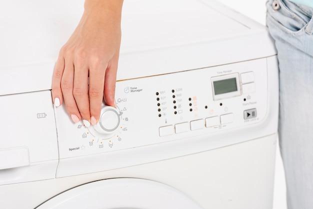 Close-upvrouw die de wasmachine plaatsen