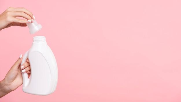 Close-upvrouw die detergent fles openen