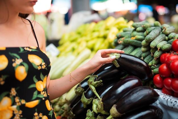 Close-upvrouw die een aubergine houden