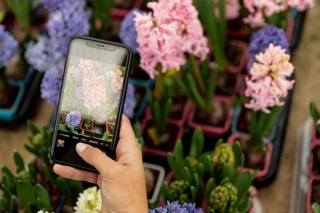 Close-upvrouw die een foto van bloemen nemen