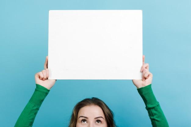 Close-upvrouw die een ruimte van het wit raadsexemplaar boven haar hoofd houden tegen blauwe muur